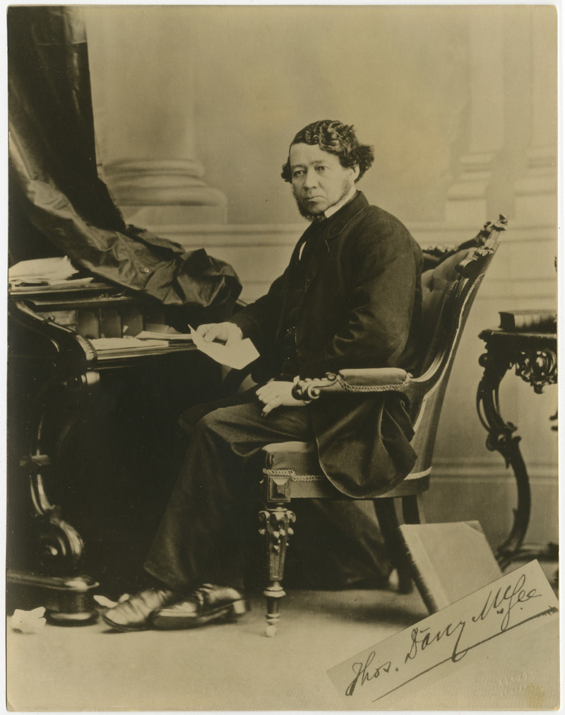 Thomas D'Arcy McGee sitting at a table.
